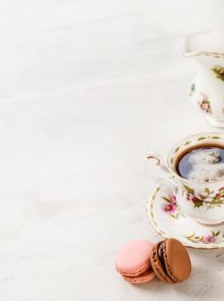 木製の背景にマカロンとセラミックコーヒーカップ