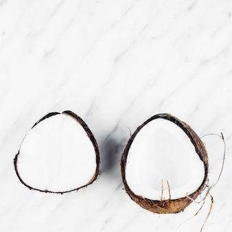 Две половинки спелого кокоса на белом фоне из мрамора