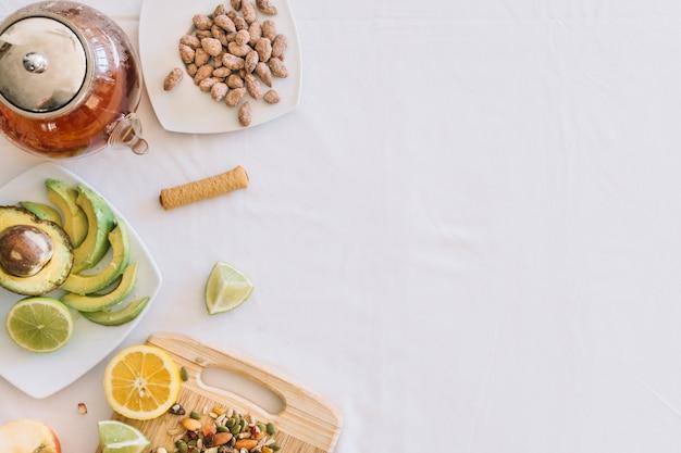 Здоровые фрукты с сушеными фруктами и чайником на белом фоне