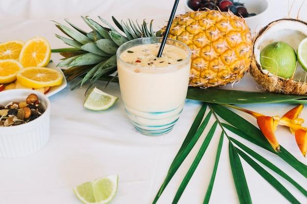 Здоровый коктейль с фруктами и сушеными фруктами на белом фоне