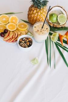 Здоровый коктейль; фрукты и сушеные фрукты на скатерти