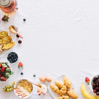 白いテーブルクロスの朝の健康的な朝食は、テキストのためのスペース