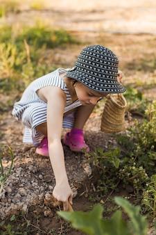 野菜の庭でうずくまる帽子をかぶっている少女
