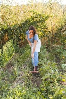 フィールドに土を掛ける女性