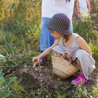 トローリングで土を掘るバスケットを持っている少女