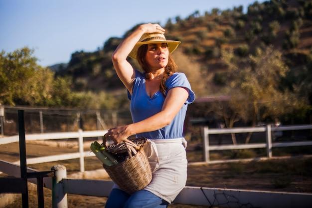 バスケットに収穫した野菜を収めた帽子をかぶってフェンスに座っている女性