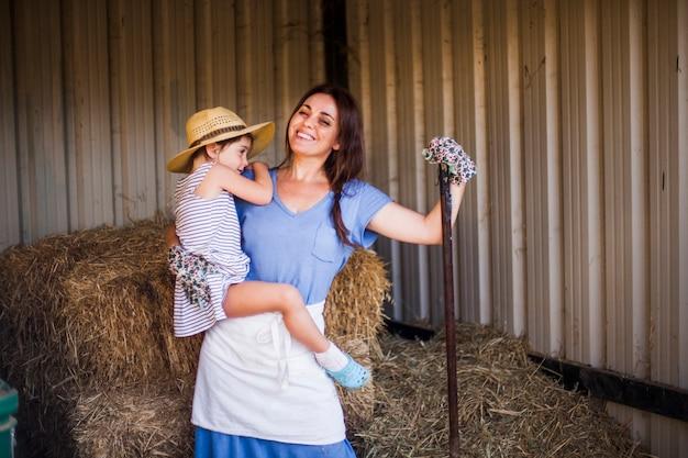 干し草の前に立つ彼女の娘を運ぶ笑顔の母