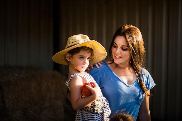 赤いリンゴを手に持つ娘を運んでいる笑顔の女性