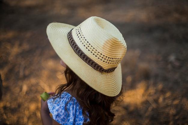 藁の帽子を身に着けている女の子のクローズアップ