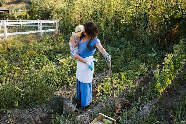 収穫された畑に立つ娘を運ぶ母親
