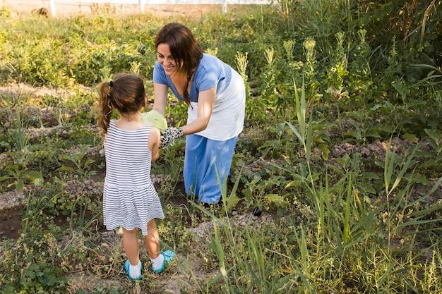 野菜の庭で彼女の娘のキャベツを与える女性