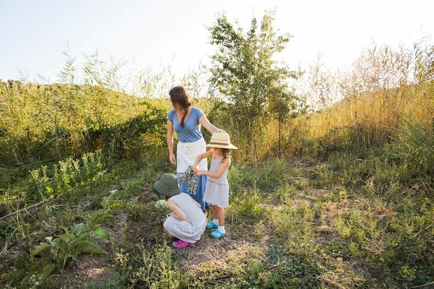 フィールドで彼女の母親と野菜を収穫している娘