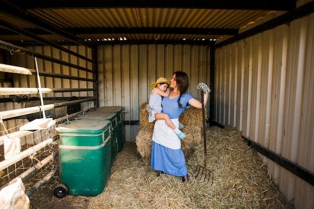 乾草の近くに立つ彼女の娘を運んでいる母親の肖像