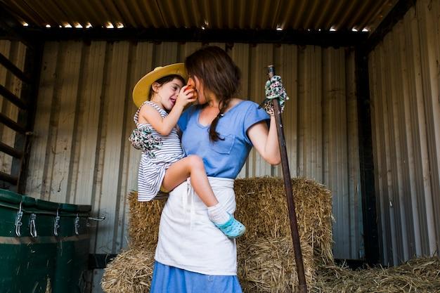 干し草の前に立っている母親に赤いリンゴを与えている娘