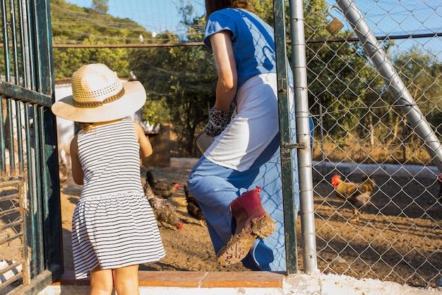 母親と娘が農場で鶏を食べる