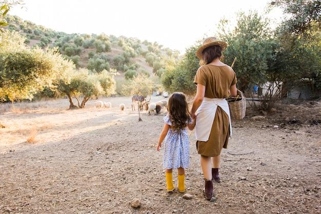 フィールドで彼女の娘と歩いている女性の背面図