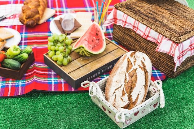 Запеченный хлеб; фрукты и корзина для пикника на торфе