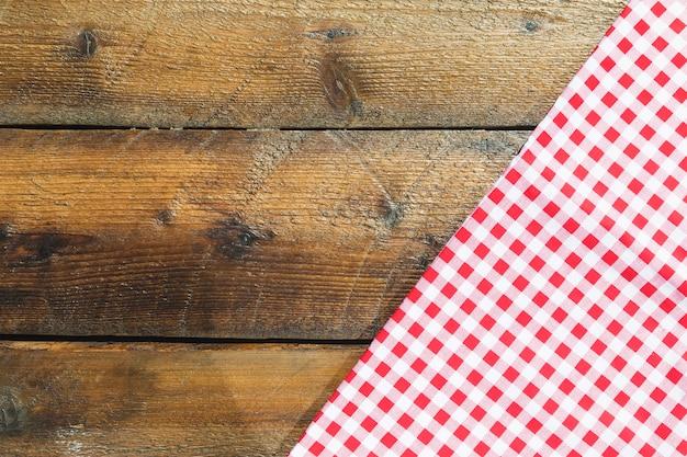 木製のテーブルの上に折り畳まれた赤いチェッカーナプキン