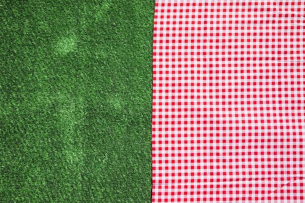 赤いチェッカーのテーブルクロスと緑の芝の背景