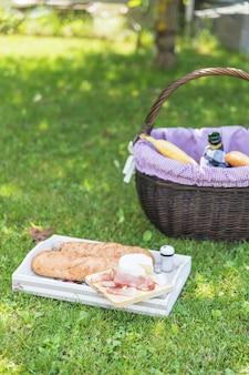 Бекон; сыр и хлеб на подносе с корзиной на зеленой траве