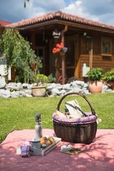 青い草の上で市松模様の毛布のピクニックバスケット