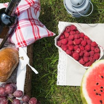 新鮮な果物と緑の草のピクニックバスケット