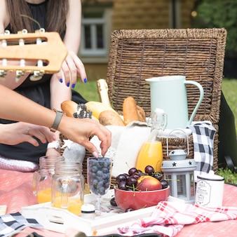 Женская рука, наслаждаясь закуской на пикнике