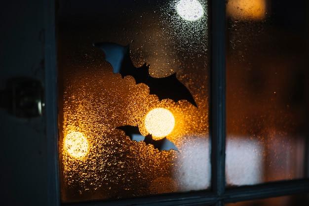 ハロウィンの装飾のコウモリが雨滴のある窓にくっついている