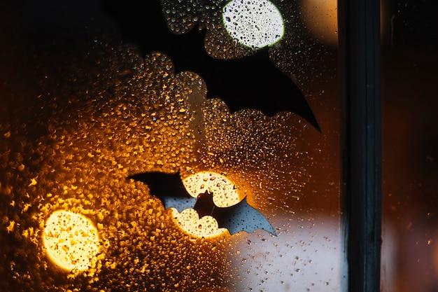 ハロウィーンの黒い装飾のコウモリが雨滴のある窓にくっついている