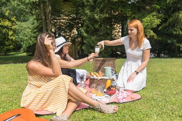 ピクニックにガラスの彼女の友人のためのビールを注ぐ幸せな女性