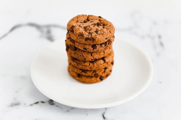 大理石の背景の上に白いプレートに焼かれたチョコレートクッキーのスタック
