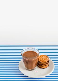 白とストライプの背景の上にプレートの上にコーヒーとクッキーのスタックのガラス