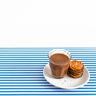 コーヒーのガラスと白とストライプの背景の上に皿のクッキーのスタック