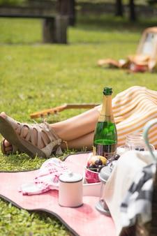 Женщина, сидящая рядом с закуской на пикнике