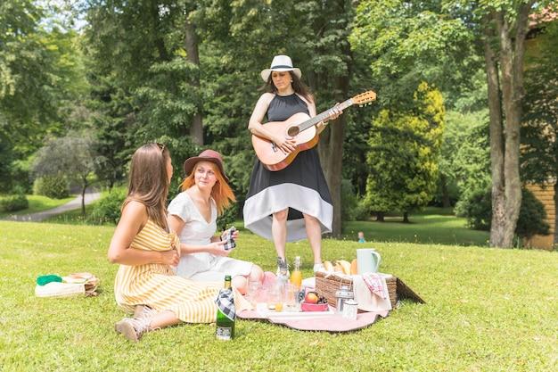 ピクニックで楽しむ彼女の友人とギターを演奏する女性