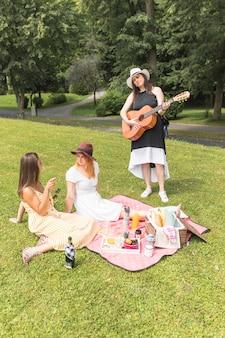 公園のピクニックで楽しむ彼女の友人のためのギターを演奏する女性