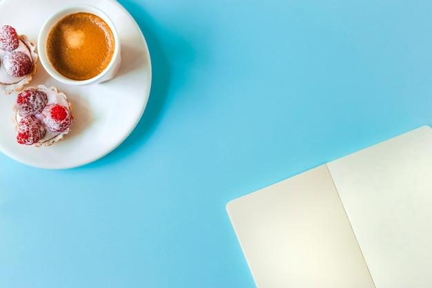 空白のページとタルト、青色の背景にコーヒーグラスで