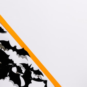 紙のストライプの後ろに置かれたハロウィーンのコウモリの群れ