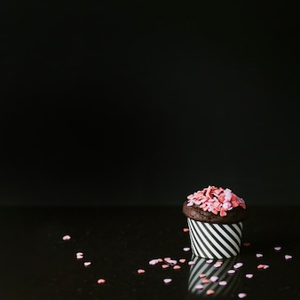 黒い背景の上にカップケーキのピンクの心の形のふりかけ