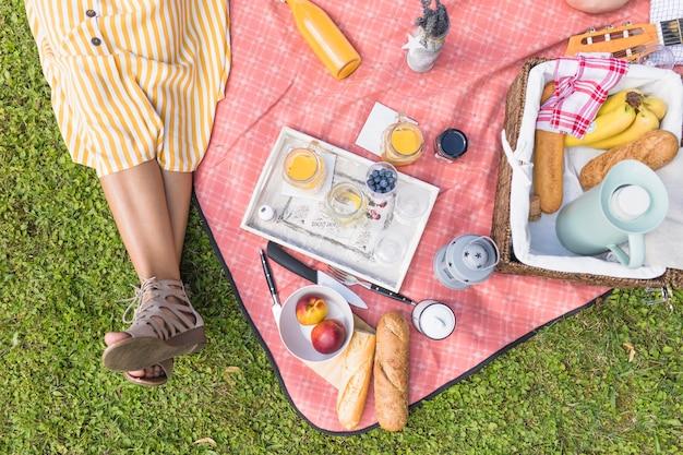 Крупным планом женщина, сидящая возле корзины для пикника на одеяле