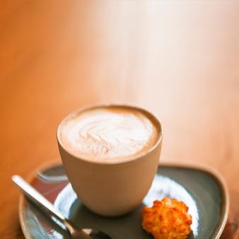 木製のテクスチャの背景にホットラテアートコーヒーのカップ