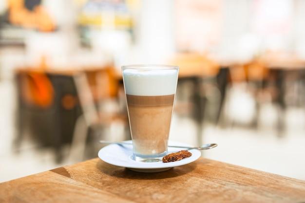 木製のテーブルにスプーンでカプチーノのコーヒーガラス