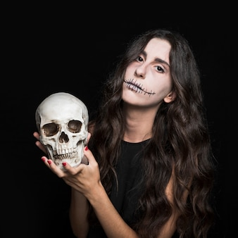 頭蓋骨を握っている灰色の女性