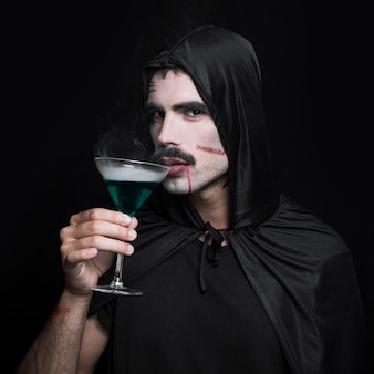 Молодой человек в черном плаще хэллоуина, ставит в студии со стаканом зеленой жидкости
