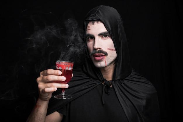 Молодой человек с царапинами на белом лицо с дымящимся напитком