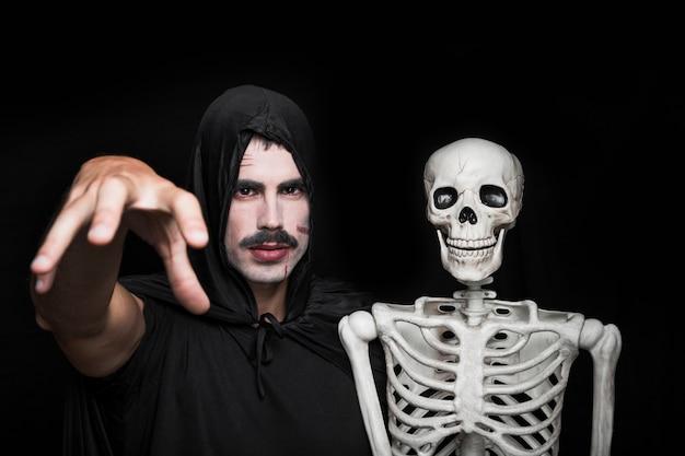 Молодой человек в черной одежде, позирует с скелетом