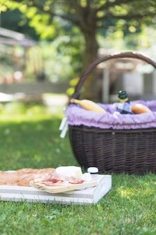 ベーコン;チーズ、パン、草の上のトレイ