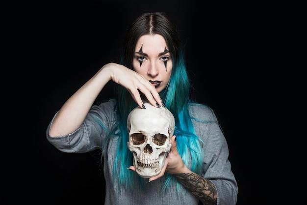 頭蓋骨で立っているクラウンメイクの若い女性