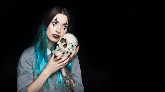 おもちゃの眼球で頭蓋骨を包む若い女性
