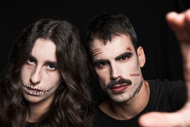 Молодые мужчины и женщины на вечеринке на хэллоуин